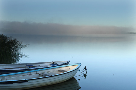 scandinavian landscape: Lake in denmark with boats and fog dissipating at the horizon Stock Photo