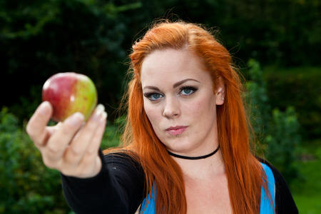 rood haar: Red hair girl in pin-up style eating an apple