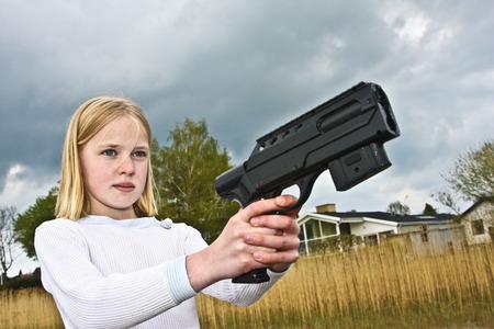 Fille jouant avec un pistolet au Danemark en été photo