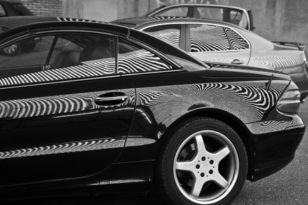Car and stripes, car parked in front of a building with striped pattern