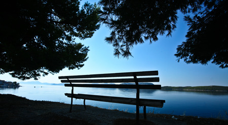 mediteranean: Trees and bench at the coast line in   Peloponese in Greece