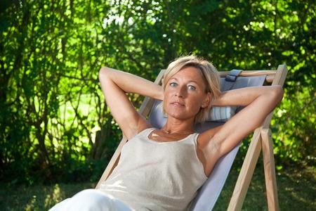 deckchair: Cute woman relaxing on a deckchair outdoor in her  garden