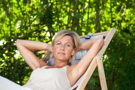 deckchair: Cute woman relaxing on a deckchair outdoor in her  garden