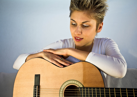 accoustic: Blond short hair woman woman with white Tshirt playing acoustic guitar Stock Photo