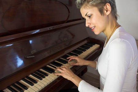 plenitude: Blond short hair woman woman with white Tshirt playing piano