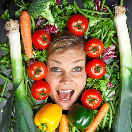 aliments droles: Funny portrait of cute blond girl  with vegetables shot in studio with vegetables aroound the head
