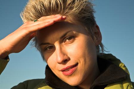Blond court cheveux femme à l'extérieur dans le soleil avec un ciel bleu en arrière-plan. Protéger ses yeux du soleil photo