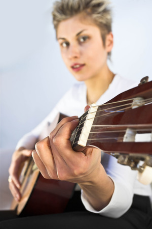 engaging: Blond short hair woman woman with white Tshirt playing acoustic guitar Stock Photo