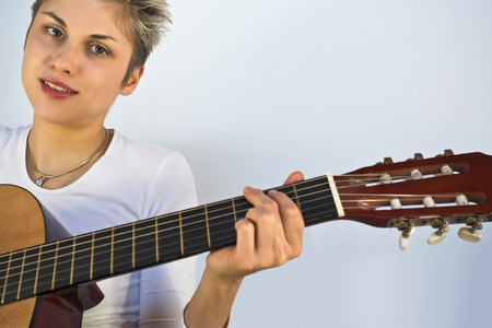 Blond short hair woman woman with white Tshirt playing acoustic guitar Stock Photo