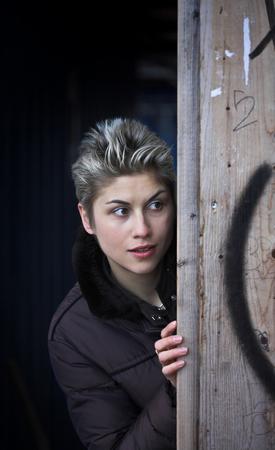 femme en plein air, en regardant la caméra, hidding derrière un mur photo