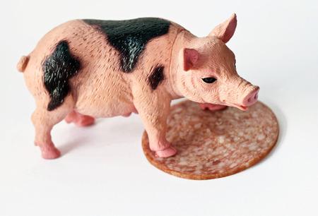 Pig plastique miniature avec une tranche de tir saussage sur fond blanc