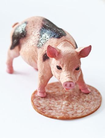 Pig plastique miniature avec une tranche de saucisson tourné sur fond blanc