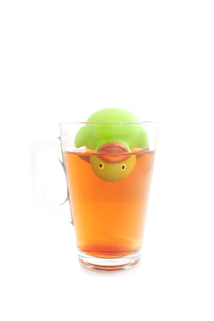 Funny rubber duck upside down in a glass tea isolated on white photo