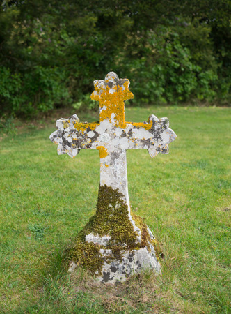 Old stone Celtic cross with moss and lichen