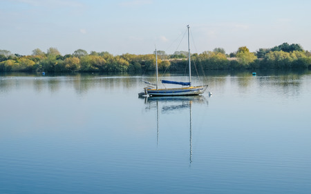 Sail boat moored on the lake on a still calm November day