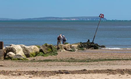 Couple climbing over the groyne on the beach