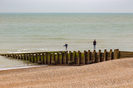 groynes: Taken when I was visiting Eastbourne in Sussex in the early summer on a cloudy day.  This young pair were balancing on the wooden posts that separate the beach areas. Stock Photo