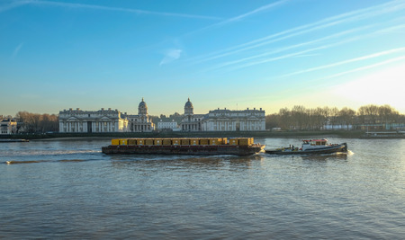 barge pulling a load of containers in front of the Royal Naval College in Greenwich Stock Photo