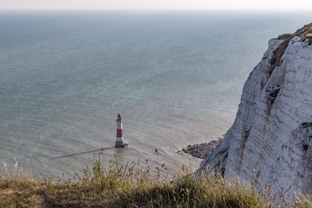 Chalk cliff looking down the the lighthouse with shadow at Beachy Head. Taken on a summers day with wild long grass in the foregroud and a side view of the cliff leading down to the lighthouse. Stock Photo