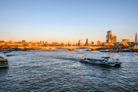 London skyline at sunset. River view with water buses and the skyline of the City.  A sunset shot.