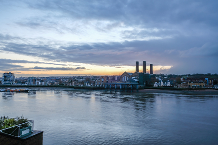 Greenwich power station at dawn. Early morning shot with the River Thames in the foreground and taken from the north side of the river looking over  southeast London.