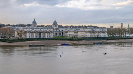 Royal Naval College, Greenwich. Shot in the early morning in winter at low tide of the Royal Naval College at Greenwich with the River Thames in the foreground and rowers.