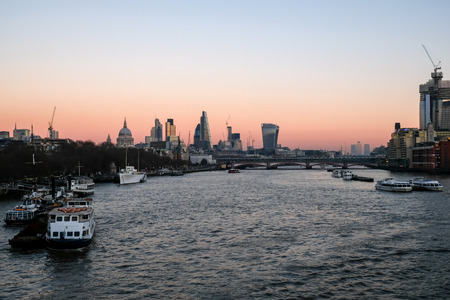 London skyline. Dusk shot of the river  Thames and the skyscrapper buildings in the City and to the East of the City at Canary Wharf. Stock Photo