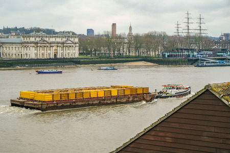 Barge pulling yellow containers passing through Greenwich with river views.  Waste disposal in London  Taken in the winter on an afternoon.