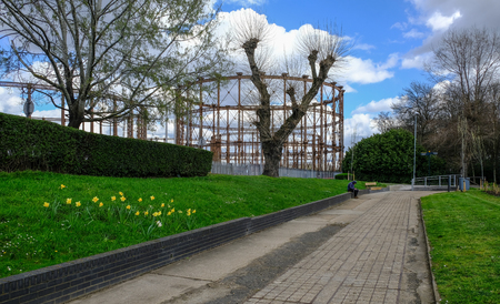 Disused gasworks in East London from pathway near River Lea.  Shows a man sitting on the wall.  A springtime shot with clouds in the sky.