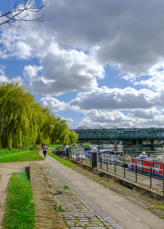 Towpath with joggers by River Lea, Bow, London.  Shows willow trees and railway bridge in spring. Stock Photo