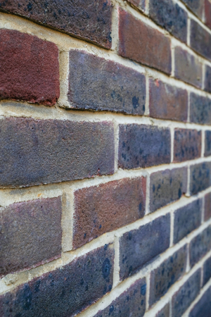 Brick wall portrait, purple and red bricks with white pointing. Stock Photo