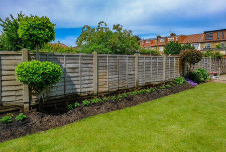 Flower bed with newly panted bedding flowers, shurbs and wooden fence Stock Photo