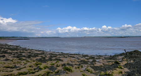 View of the river Severn crossing with old Severn bridge.  Low tide and sandy shore in the foreground. Stock Photo