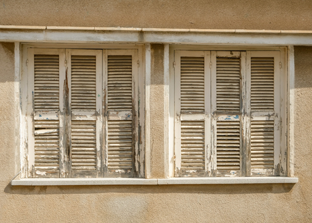 Old Windows with closed worn shutters
