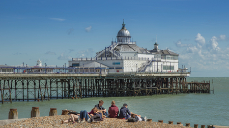 Eastbourne, Sussex, England - August 8, 2014:  Eastbourne Pier with young people in the foreground on the beach.
