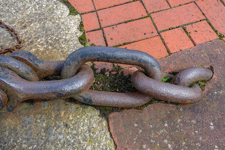 Large rusty link industrial chain close-up with metal joint.