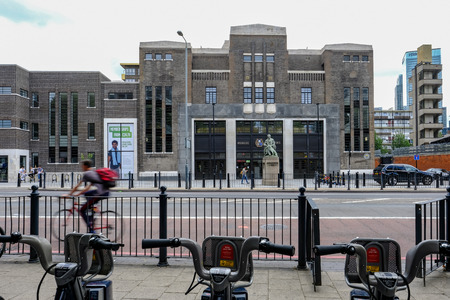 Poplar, London, UK - July 16, 2017:  Poplar Baths, regenerated looking from Chrisp Street with Boris bikes in the foreground.
