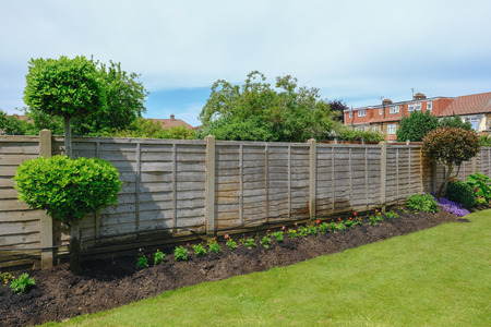 Flower bed with garden fence and lawn, taken in early summer.