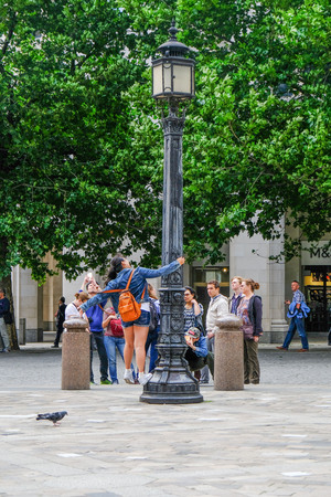 bollard: London, Uk - August 3, 2017: Young girl posing on a lamp post with group of tourists taking a photo. A daytime shot of a street scene.