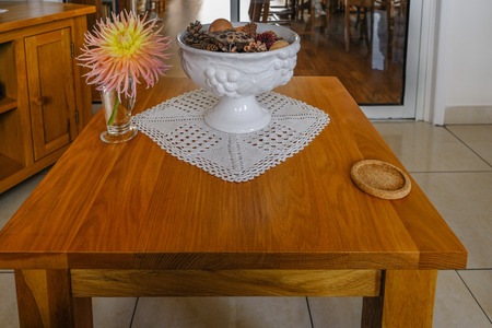 Oak coffee table with coaster, bowl and dalhia flower in vase. Modern living room closeup.