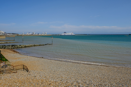 stoney: Dover, Kent, UK - August 17, 2017:Dover beach and harbour with Ferry departing. Summer shot from the beach.