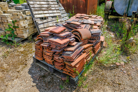 Old abandoned clay roof tiles lying on a pallet in an old yard.  Stack of bricks in the background.
