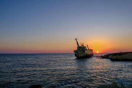 Sunset of shipwreck listing by rocks in the sea near Pafos, Cyprus.  Evening shot with two people on the rocks giving scale.