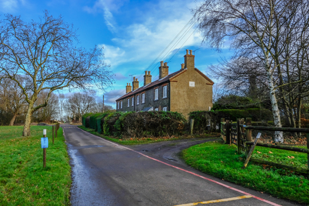 Hainault Forest, Essex, England, UK  - December 26, 2017: Row of cottages in Epping Forest, used for rangers, taken on a bright blue sky day.