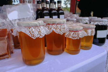 Closeup view of a selection of honey in jars with lacy tops displayed at a village fete.