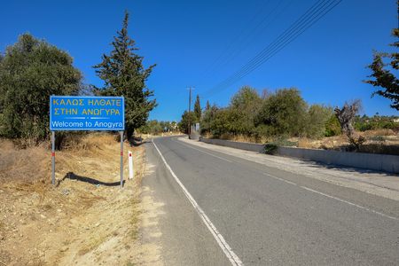 Sign of welcome to Anoyira on an empty road as you approach the village, also written in greek. Stock Photo