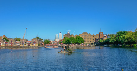 Shadwell Basin, London, UK - May 7, 2018:  View of the basin on a sunny day wiht many people sunbathing and swimming with Canary Wharf in the background.