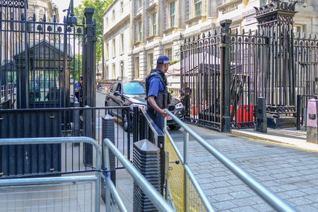 Downing Street, London, UK - June 8, 2018: Armed police protecting the black steel gated entrance to Downing Street.  Shows a car being allowed out.