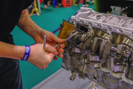 Excel, London, UK - February, 16, 2018: Hands of engineer building an engine at a car show exhibition.