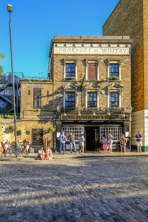 Wapping, London, UK - May 7, 2018:Portrait shot of the Prospect of Whitby Pub in Wapping with people enjoying the sunshine outside. Afternoon shot with lovely light.